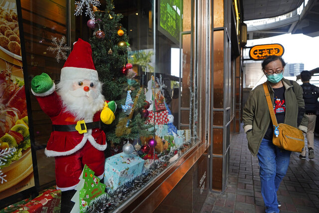 A man wearing a face mask to protect against the spread of the coronavirus walks past Christmas decorations in a restaurant window in Hong Kong, Friday, Dec. 11, 2020. (AP Photo/Kin Cheung)