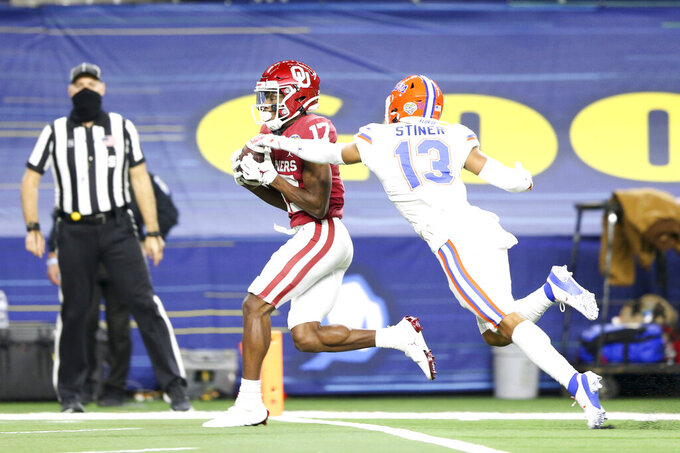 Oklahoma wide receiver Marvin Mims (17) catches a touchdown while being defended by Florida defensive back Donovan Stiner (13) during the Goodyear Cotton Bowl between Oklahoma and Florida at AT&T Stadium in Arlington, Texas on Wednesday, Dec. 30, 2020.(Ian Maule/Tulsa World via AP)