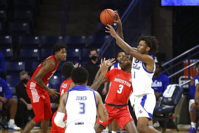 Tulsa's Brandon Rachal is defended by Houston's Marcus Sasser and DeJon Jarreau (3) as Tulsa's Elijah Joiner watches during the second half of an NCAA college basketball game in Tulsa, Okla., Tuesday, Dec. 29, 2020. Tulsa won 65-64. (AP Photo/Dave Crenshaw)
