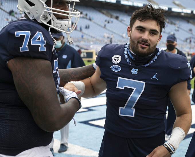 North Carolina's Jordan Tucker (74) embraces quarterback Sam Howell (7) following their 56-49 victory over Virginia Tech  in an NCAA college football game, Saturday, Oct. 10, 2020 at Kenan Stadium in Chapel Hill, N.C. (Robert Willett/The News & Observer via AP)