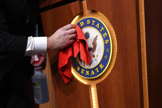 Mike Mastrian, Director of the Senate Radio and Television Gallery, cleans down the podium before a news conference with Senate Majority Leader Mitch McConnell of Ky., on Capitol Hill in Washington, Tuesday, March 17, 2020. (AP Photo/Susan Walsh)