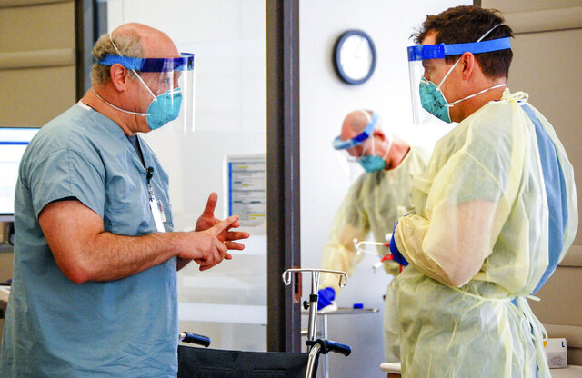 Dr. Michael Saag, left, speaks with an unidentified coworker in Birmingham, Ala., on Friday, July 10, 2020. Saag survived COVID-19 and now treats patients with the disease. (Amanda Chambers/University of Alabama at Birmingham via AP)
