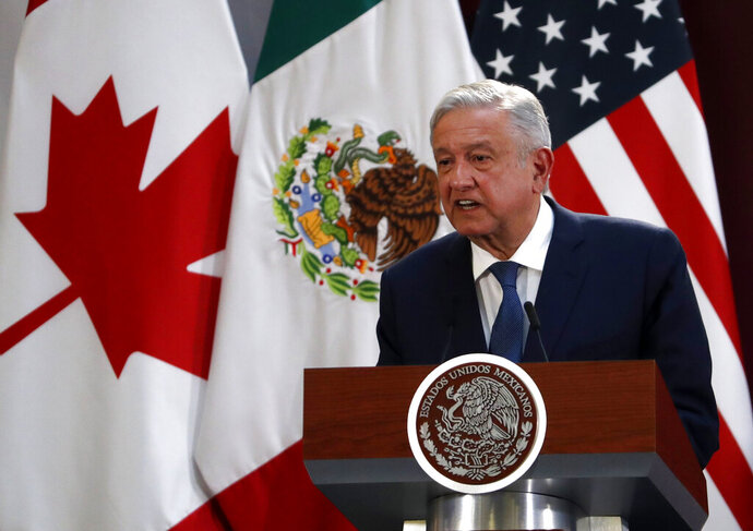 FILE - In this Dec. 10. 2019 file photo, Mexico's President Andres Manuel Lopez Obrador speaks during an event to sign an update to the North American Free Trade Agreement, at the National Palace in Mexico City. Mexico celebrated on Wednesday, July 1, 2020, the implementation of the new free trade agreement with Canada and the United States that it hopes will lead to more investment in its struggling economy. (AP Photo/Marco Ugarte, File)