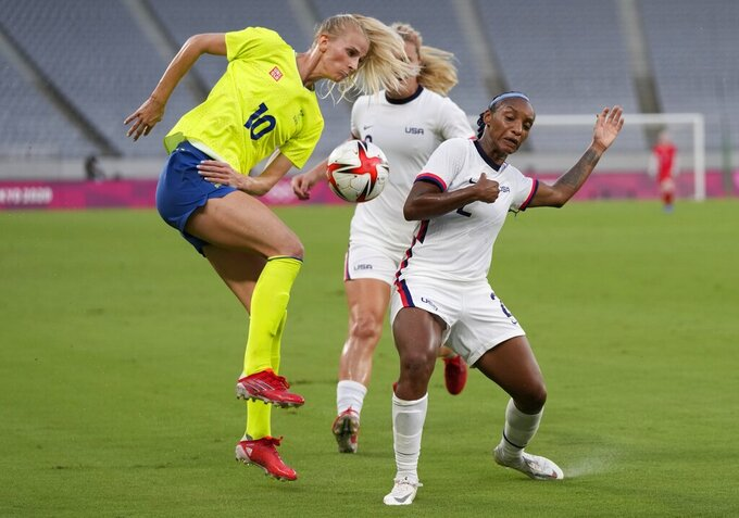 United States' Crystal Dunn, right, and Sweden's Sofia Jakobsson, left, fight for the ball during a women's soccer match at the 2020 Summer Olympics, Wednesday, July 21, 2021, in Tokyo. (AP Photo/Ricardo Mazalan)