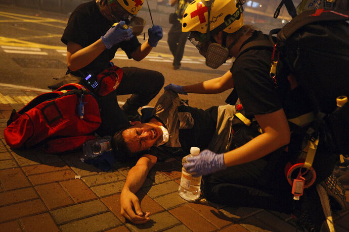 "FILE - In this file photo taken Sunday, July 21, 2019, medical workers help a protester in pain from tear gas fired by policemen on a street in Hong Kong.  The former British colony of Hong Kong was returned to China in 1997 under a ""one country, two systems"" concept that gives the city a fair degree of autonomy over its affairs, but China may intervene to quell protests now in their seventh week. (AP Photo/Bobby Yip, File)"