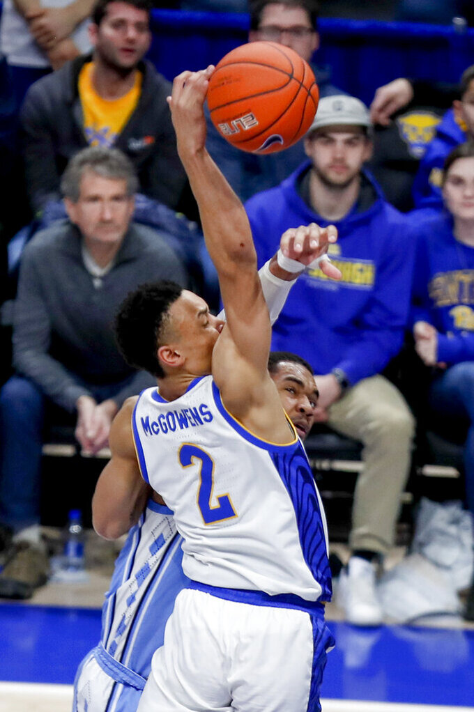 Pittsburgh's Trey McGowens (2) tries to go over North Carolina's Garrison Brooks, but lost the ball as he was fouled by Brooks during the second half of an NCAA college basketball game, Saturday, Jan. 18, 2020, in Pittsburgh. Pittsburgh won 66-52. (AP Photo/Keith Srakocic)