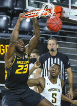 Missouri's Jeremiah Tilmon (23) dunks over Wichita State's Trey Wade during the first half of an NCAA college basketball game Sunday, Dec. 6, 2020, in Wichita, Kan. (Travis Heying/The Wichita Eagle via AP)