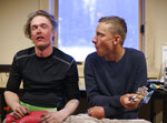 In this Tuesday evening, May 21, 2019 photo, snowboarder John Moser, left, catches his breath next to his friend Patrick Powers after being rescued at Arapahoe Basin Ski Area, in Dillon, Colo.  Moser, who was found by Summit County Rescue Group and the ski patrol, was swept up by an avalanche as he and his friend Patrick Powers were attempting to hike back inbounds. (Hugh Carey/Summit Daily News via AP)