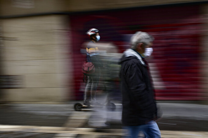 A pedestrian and a person using a scooter wear face mask protection to prevent the spread of COVID-19 during an autumn day in Pamplona, northern Spain, Friday, Sept. 25, 2020. (AP Photo/Alvaro Barrientos)