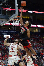 Louisville forward Dwayne Sutton (24) reaches for a rebound over Western Kentucky guard Camron Justice (5) during the first half of an NCAA college basketball game Friday, Nov. 29, 2019, in Nashville, Tenn. (AP Photo/Mark Zaleski)
