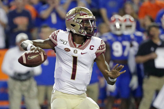 FILE - Florida State quarterback James Blackman looks for a receiver during the first half of the team's NCAA college football game against Florida, in Gainesville, Fla., Saturday, Nov. 30, 2019. Florida State coach Mike Norvell named James Blackman his starting quarterback to open the season. Blackman got the nod Tuesday, Sept. 1, 2020, after beating out Louisville transfer Jordan Travis and freshman Tate Rodemaker during fall camp. (AP Photo/John Raoux, File)
