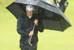 Brooks Koepka of the United States walks onto the 10th green as he shelters from the heavy rain under an umbrella during the final round of the British Open Golf Championships at Royal Portrush in Northern Ireland, Sunday, July 21, 2019.(AP Photo/Jon Super)