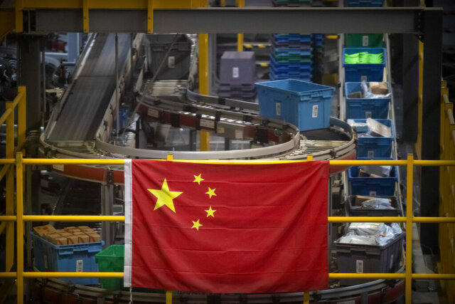 FILE - In this Nov. 11, 2020, file photo a Chinese flag hangs near an automated parcel handling line at a warehouse for an online retailer in Beijing. President Donald Trump has identified China as the country's biggest foe and the Justice Department mirrored that emphasis over the last four years with a drumbeat of cases against defendants ranging from hackers accused of targeting intellectual property to professors charged with grant fraud. (AP Photo/Mark Schiefelbein, File)