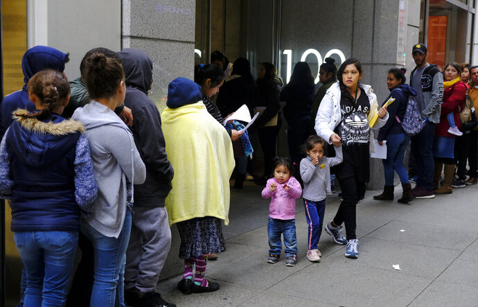 File - In this Jan. 31, 2019, file photo, hundreds of people overflow onto the sidewalk in a line snaking around the block outside a U.S. immigration office with numerous courtrooms in San Francisco. Santa Clara and San Francisco have filed suit against the Trump administration over its new controversial