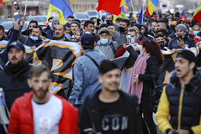 People protesting against the COVID-19 pandemic restrictions march in downtown Bucharest, Romania, Monday, March 29, 2021. Thousands of anti-restriction protesters took to the streets in several cities across Romania on Monday evening, a day after new restriction measures came into force. (AP Photo/Vadim Ghirda)