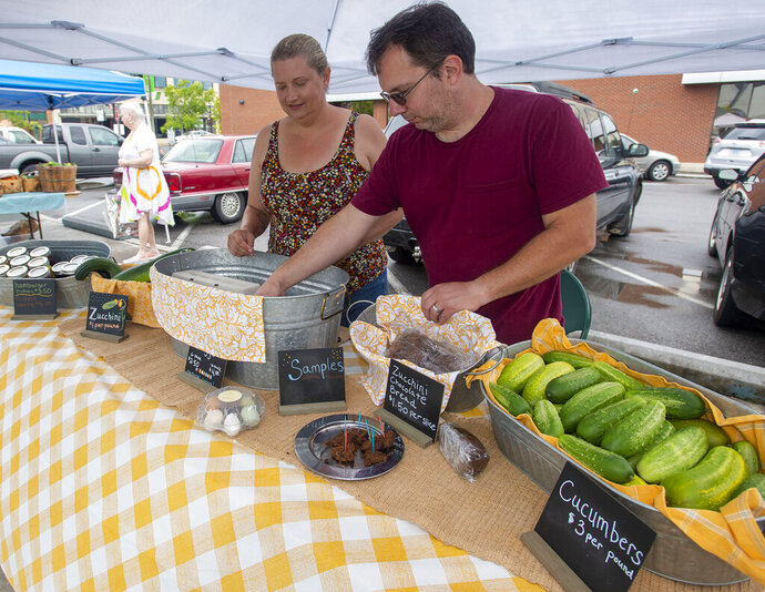In this July 17, 2019 photo, Jerry and Ingrid Gagnon, owners of Castlewood Grove Farm, set up at the State Street Farmer's Market in Bristol, Tenn. This couple sells chocolate zucchini bread, pickles, jam, eggs and pickled beets _ all products from their 21-acre Castlewood Grove Farm on Copper Ridge Road.(David Crigger/Bristol Herald Courier via AP)