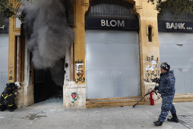 FILE - In this Tuesday, Feb. 11, 2020 file photo, a firefighter looks before entering a bank that was set on fire by anti-government protesters, as a riot policeman passes by, during a protest in downtown Beirut, Lebanon. Fitch Ratings said Tuesday, Feb. 18, 2020, that Lebanon's financial position points to a likely restructuring of the country's massive debt and financial sector as the Arab nation passes though its worst financial and economic crisis in decades. (AP Photo/Hussein Malla, File)