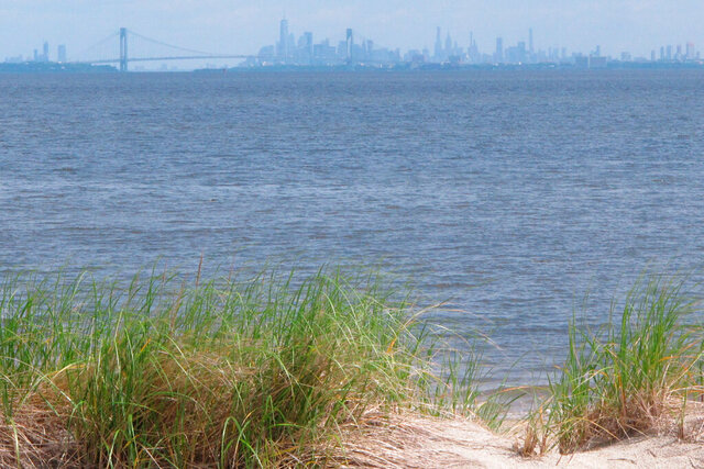 FILE – In this June 3, 2019 file photo, the New York City skyline is seen behind Raritan Bay from Middletown, N.J. On Thursday, Feb. 20, 2020, Oklahoma-based Williams Companies said it is resuming its effort to gain approval from New Jersey environmental regulators for a nearly $1 billion pipeline that would bring natural gas from Pennsylvania through New Jersey, out into Raritan Bay and into the ocean before reaching New York and Long Island. (AP Photo/Wayne Parry, File)