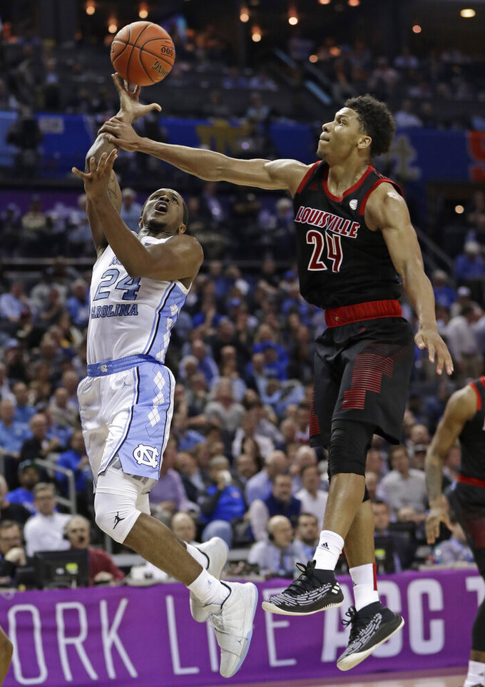 North Carolina's Kenny Williams, left, is fouled by Louisville's Dwayne Sutton, right, during the second half of an NCAA college basketball game in the Atlantic Coast Conference tournament in Charlotte, N.C., Thursday, March 14, 2019. (AP Photo/Nell Redmond)