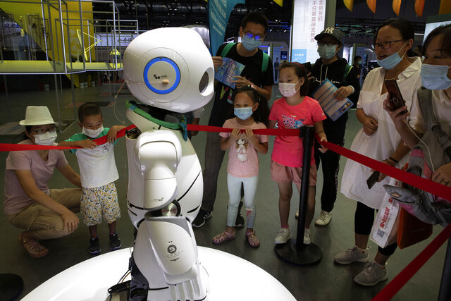 Visitors wearing masks to protect from the coronavirus look at a robot displayed at a trade fair in Beijing on Sunday, Sept. 6, 2020. China's export growth accelerated in August while imports edged lower as the world's second-largest economy extended its recovery from the coronavirus pandemic. (AP Photo/Ng Han Guan)