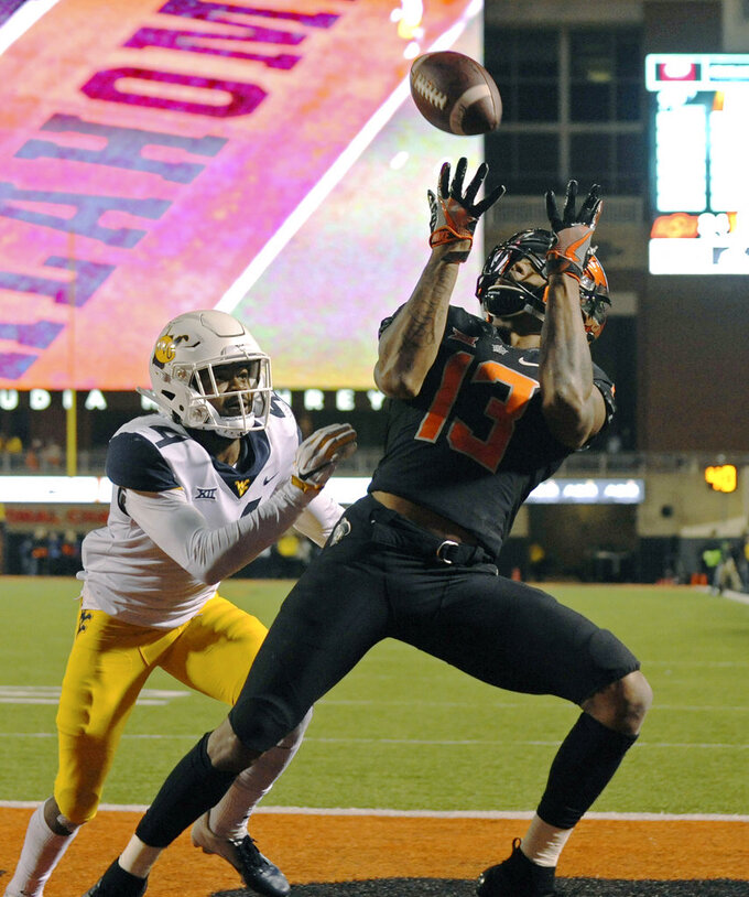 Oklahoma State wide receiver Tyron Johnson (13) catches a touchdown pass while under pressure from West Virginia cornerback Josh Norwood during the second half of an NCAA college football game in Stillwater, Okla., Saturday, Nov. 17, 2018. Oklahoma State upset West Virginia 45-41.(AP Photo/Brody Schmidt)
