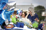 Terrie Dyer wipes a tear as she prays at a makeshift memorial for Tulsa Police Officers Craig Johnson and Aurash Zarkeshan at Mingo Valley Division Tuesday, June 30, 2020. The officers were shot early Monday morning during a traffic stop.  (Mike Simons/Tulsa World via AP)