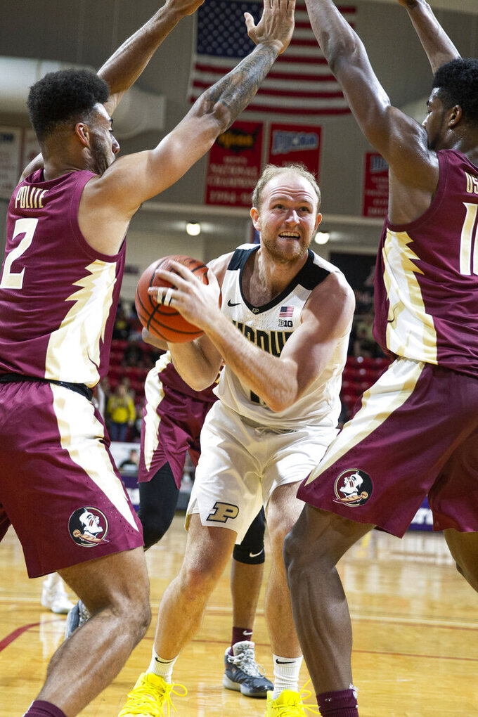 Purdue forward Evan Boudreaux (12) looks to shoot between Florida State guard Anthony Polite (2) and forward Malik Osborne (10) in the first half of an NCAA college basketball game at the Emerald Coast Classic in Niceville, Fla., Saturday, Nov. 30, 2019. (AP Photo/Mark Wallheiser)