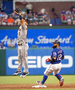 Houston Astros shortstop Alex Bregman (2) misses the relay throw as Texas Rangers' Rougned Odor (12) cruises into second with a double during the third inning of a baseball game Thursday, July 11, 2019, in Arlington, Texas. (AP Photo/Jeffrey McWhorter)
