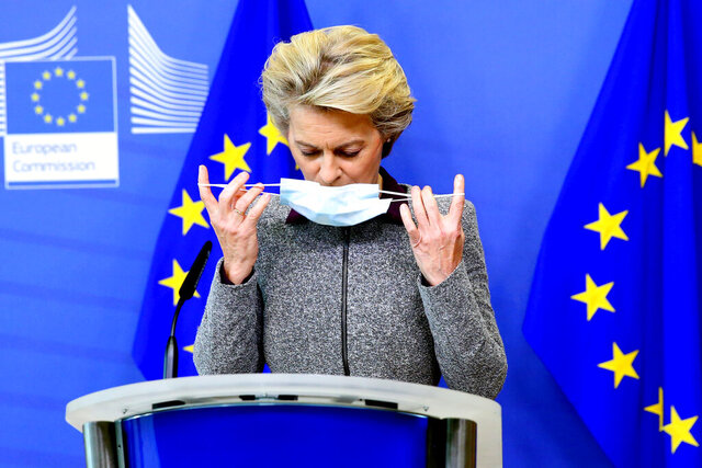President of the European Commission Ursula von der Leyen takes off her protective face mask prior to speaking during a media conference at EU headquarters in Brussels, Thursday, Aug. 27, 2020. The European Commission president said Thursday her team could face a reshuffle after the resignation of the Irish trade Commissioner, Phil Hogan, over a controversy involving his questionable adherence to COVID-19 rules. (Francois Walschaerts, Pool Via AP)