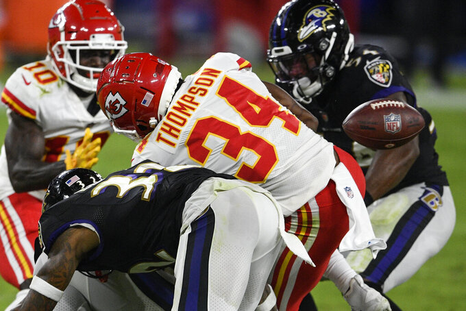 Kansas City Chiefs running back Darwin Thompson (34) is hit by Baltimore Ravens strong safety Chuck Clark (36) and free safety DeShon Elliott (32) to cause a fumble during the second half of an NFL football game, Monday, Sept. 28, 2020, in Baltimore. (AP Photo/Nick Wass)
