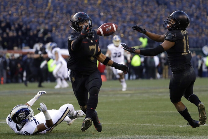 Army's Jaylon McClinton, center, intercepts a pass tipped by teammate Mike Reynolds, right, that was intended for Navy's Mychal Cooper during the first half of an NCAA college football game, Saturday, Dec. 8, 2018, in Philadelphia. (AP Photo/Matt Slocum)
