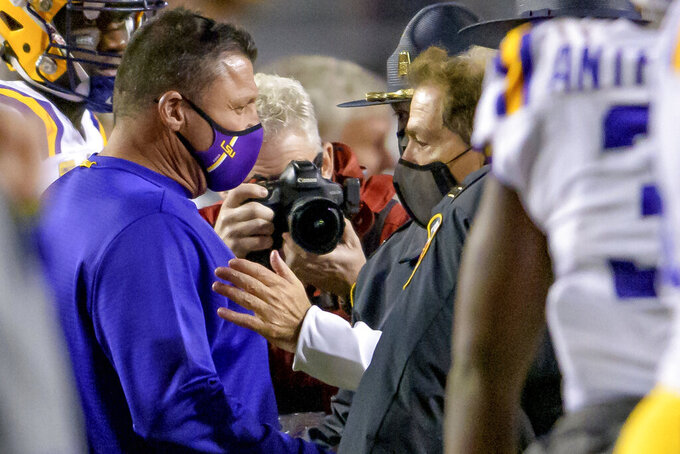 Alabama coach Nick Saban, right, greets LSU coach Ed Orgeron after Alabama's victory in an NCAA college football game in Baton Rouge, La., Saturday, Dec. 5, 2020. (AP Photo/Matthew Hinton)