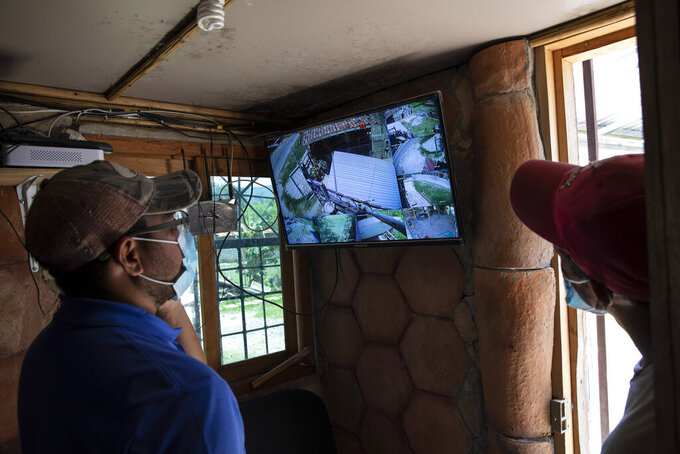 Seminarians monitor security cameras at the mission and drug rehab center run by Friar Leopoldo Serrano, located in a valley marked by poverty and drug violence, in Mission San Francisco de Asis, Honduras, Thursday, June 24, 2021. Serrano who is routinely observed by men passing by in oversized SUVs with tinted windows, complained to the prosecutor's office which led to the installation of surveillance systems. (AP Photo/Rodrigo Abd)