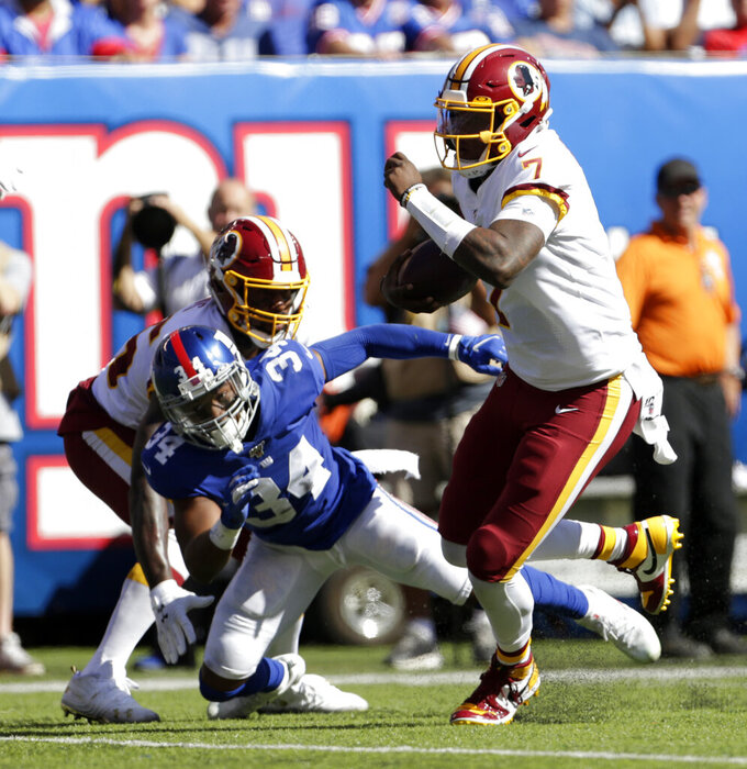 Washington Redskins quarterback Dwayne Haskins, right, runs the ball during the first half of an NFL football game against the New York Giants, Sunday, Sept. 29, 2019, in East Rutherford, N.J. (AP Photo/Adam Hunger)