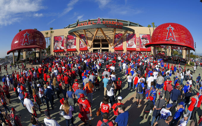FILE - In this April 4, 2016, file photo, fans line up outside Angel Stadium of Anaheim for an opening day baseball game between the Los Angeles Angels and the Chicago Cubs, in Los Angeles. It used to be that empty seats caused palpitations in team owners and college administrators relying on ticket sales and concessions to beef up the profit margins. Now, those empty seats – and short lines and clear concourses – will be the norm for a while as sports grapples with social distancing requirements. (AP Photo/Mark J. Terrill)