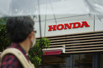 A man wearing a protective mask to help curb the spread of the coronavirus walks past the logo of Honda Motor Company Thursday, May 13, 2021, in Tokyo. Honda swung into the black in January-March, recording a 213 billion yen ($2 billion) profit, despite the ongoing uncertainties unleashed by the coronavirus pandemic, the results, released Friday, May 14, 2021. (AP Photo/Eugene Hoshiko)