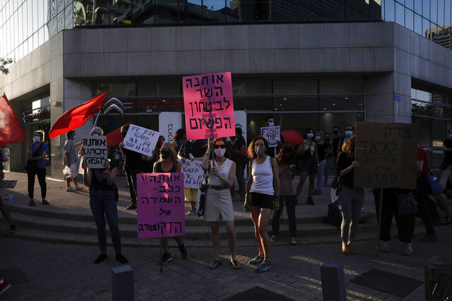 Israelis chant slogans during a demonstration against corruption near the house of Israel's Minister of Public Security In Tel Aviv, Israel, Thursday, July 30, 2020. Sign in Hebrew reads: