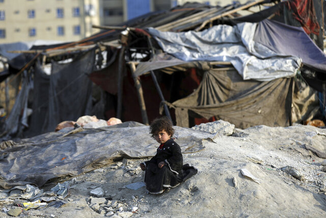 An internally displaced girl poses for photograph outside her temporary home in the city of Kabul, Afghanistan, Monday, Jan. 18, 2021. Half of war-ravaged Afghanistan's population is at risk of not having enough food to eat, including around 10 million children, Save the Children, a humanitarian organization said Tuesday. The group called for $3 billion in donations to pay for assistance in 2021. (AP Photo/Rahmat Gul)