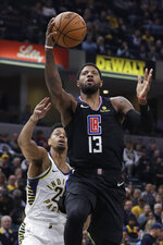 Los Angeles Clippers' Paul George (13) puts up a shot against Indiana Pacers' Jeremy Lamb during the first half of an NBA basketball game, Monday, Dec. 9, 2019, in Indianapolis. (AP Photo/Darron Cummings)