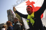 A man waves a flag near the Notre Dame Cathedral as he takes part in a yellow vest demonstration in Paris, Saturday, April 20, 2019. French yellow vest protesters are marching anew to remind the government that rebuilding the fire-ravaged Notre Dame Cathedral isn't the only problem the nation needs to solve. (AP Photo/Francisco Seco)