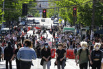 People walk past barricades on a street near Cal Anderson Park, Thursday, June 11, 2020, inside what is being called the