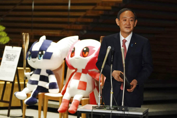 Japanese Prime Minister Yoshihide Suga, next to the mascots of Tokyo 2020 Olympic and Paralympic Games, speaks to media after a government task force meeting for the new virus measures, at the prime minister's office Friday, April 9, 2021, in Tokyo. Japan announced Friday that it will raise the coronavirus alert level in Tokyo to allow tougher measures to curb the rapid spread of a more contagious variant ahead of the Summer Olympics. (AP Photo/Eugene Hoshiko, Pool)