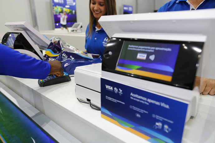 "In this June 30, 2016, image taken by AP Images for Visa, Team Visa athlete Popole Misenga uses his Visa payment ring at the Copacabana Megastore in Rio de Janeiro, Brazil.  Payment networks and manufacturers are building payment functions into more devices — expanding your options as well as freeing up your hands. Connected ""smart"" accessories such as watches, bands and rings travel lighter than a phone. To use, the wearer holds a wrist or hand up to a contactless payment terminal. Visa tested these devices at the 2016 Rio Olympics to demonstrate possibilities, says Mark Jamison, global head of innovation and design at Visa. (Leo Correa/AP Images for Visa)"