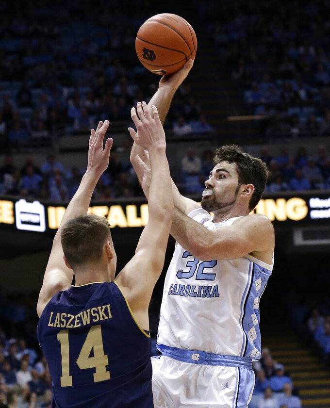 North Carolina's Luke Maye (32) shoots while Notre Dame's Nate Laszewski (14) defends during the first half of an NCAA college basketball game in Chapel Hill, N.C., Tuesday, Jan. 15, 2019. (AP Photo/Gerry Broome)