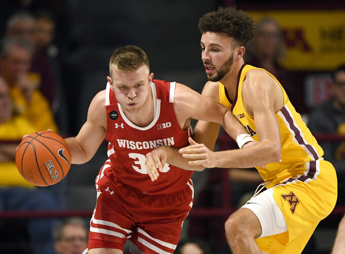 Wisconsin's Brad Davison (34) dribbles next to Minnesota's Gabe Kalscheur (22) during the first half of an NCAA college basketball game Wednesday, Feb. 5, 2020, in Minneapolis. (AP Photo/Hannah Foslien)