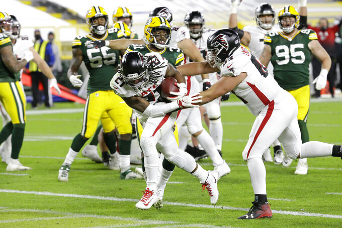Atlanta Falcons' Todd Gurley (21) runs for a touchdown during the second half of an NFL football game against the Green Bay Packers, Monday, Oct. 5, 2020, in Green Bay, Wis. (AP Photo/Mike Roemer)