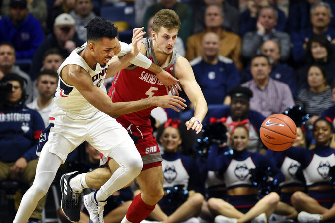 Connecticut's Tyler Polley (12) chases the ball with Sacred Heart's Zach Pfaffenberger (5) in the first half of an NCAA college basketball game, Friday, Nov. 8, 2019, in Storrs, Conn. (AP Photo/Stephen Dunn)