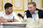 FILE In this file photo taken on Monday, June 3, 2019 provided by the Ukrainian Presidential Press Office, Ukrainian president Volodymyr Zelenskiy, left, listens to former Ukrainian president Leonid Kuchma, a special Ukrainian presidential envoy in the contact group for talks on a cease-fire in Eastern Ukraine, during their meeting in Kiev, Ukraine. Ukraine's president sits down Monday, Dec. 9, 2019 for peace talks in Paris with Russian President Vladimir Putin in their first face-to-face meeting, and the stakes could not be higher. More than five years of fighting in eastern Ukraine between government troops and Moscow-backed separatists has killed more than 14,000 people, and a cease-fire has remained elusive. (Ukrainian Presidential Press Office via AP, File)