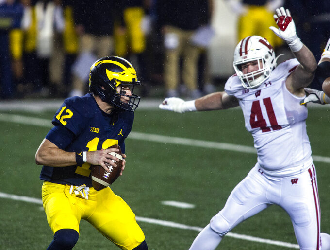 Michigan quarterback Cade McNamara (12) is pressured by Wisconsin outside linebacker Noah Burks (41) in the fourth quarter of an NCAA college football game in Ann Arbor, Mich., Saturday, Nov. 14, 2020. (AP Photo/Tony Ding)