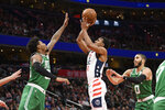 Washington Wizards guard Ish Smith, center, shoots between Boston Celtics guard Marcus Smart, left, and forward Jayson Tatum (0) during the first half of an NBA basketball game, Monday, Jan. 6, 2020, in Washington. The Wizards won 99-94. (AP Photo/Nick Wass)